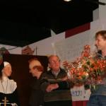 Mark van Raalte (vz bestuur Ons Dorpshuis Wilhelminaoord) overhandigt de bloemen na een geslaagde voorstelling.